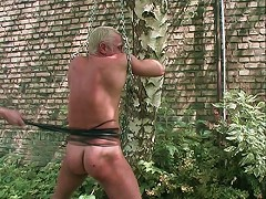 Ass flogged and caned in gay BDSM outdoors